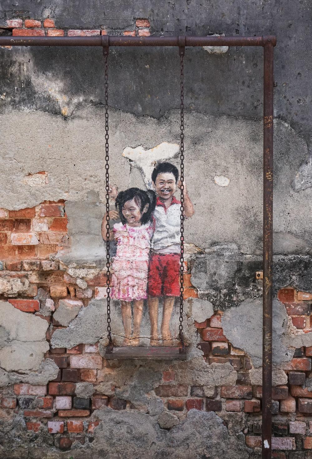 curio.trips.malaysia.penang.street.art.girl.boy.swing.portrait.jpg