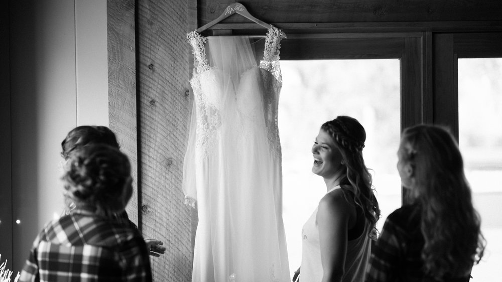 Wedding dress hangs on door bride laughs in foreground.