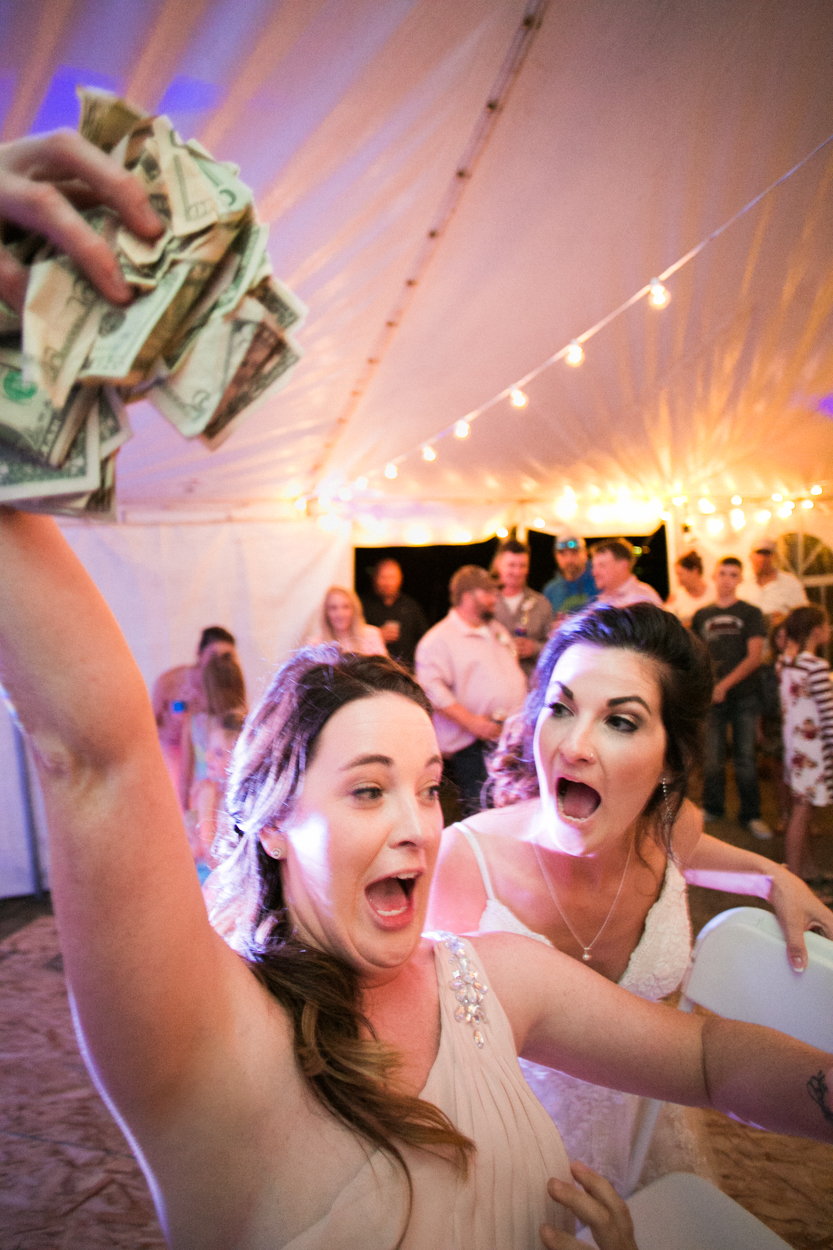 Girl with hand full of money running with bride at wedding dance.