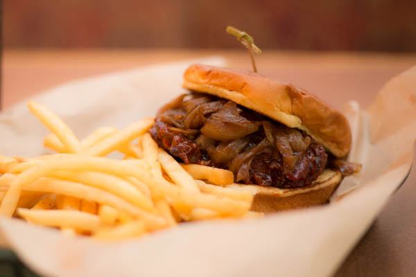 BBQ Beef Brisket covered with caramelized onions and a side of french fries.