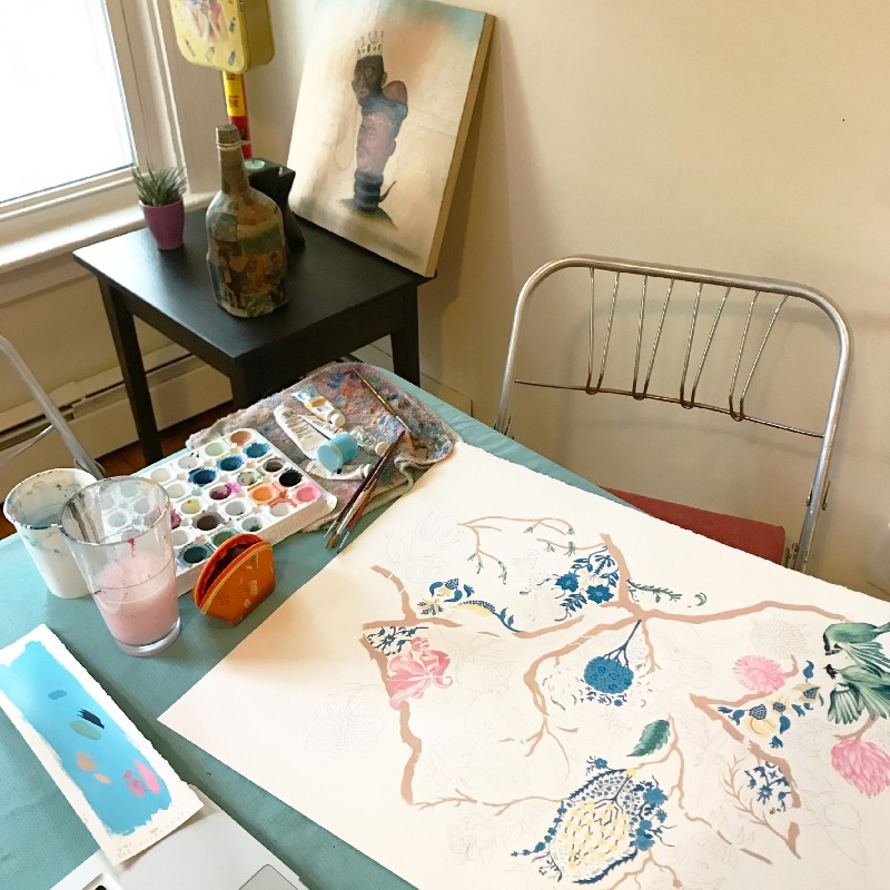 A typical set-up for my painting process: a flat surface, water, brushes, paint, and an eraser (pictured in pouch). The natural light is an added bonus.