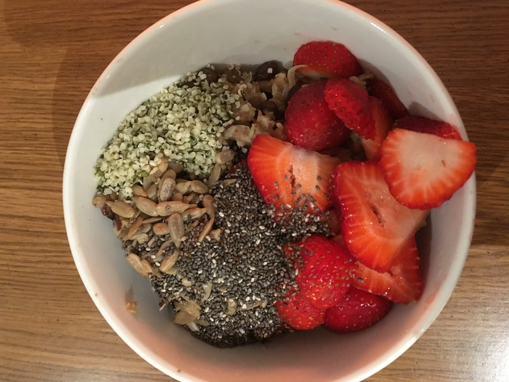 The final product, topped with sunflower seeds, hemp seeds, chia seeds, almond milk, maple syrup and fresh strawberries