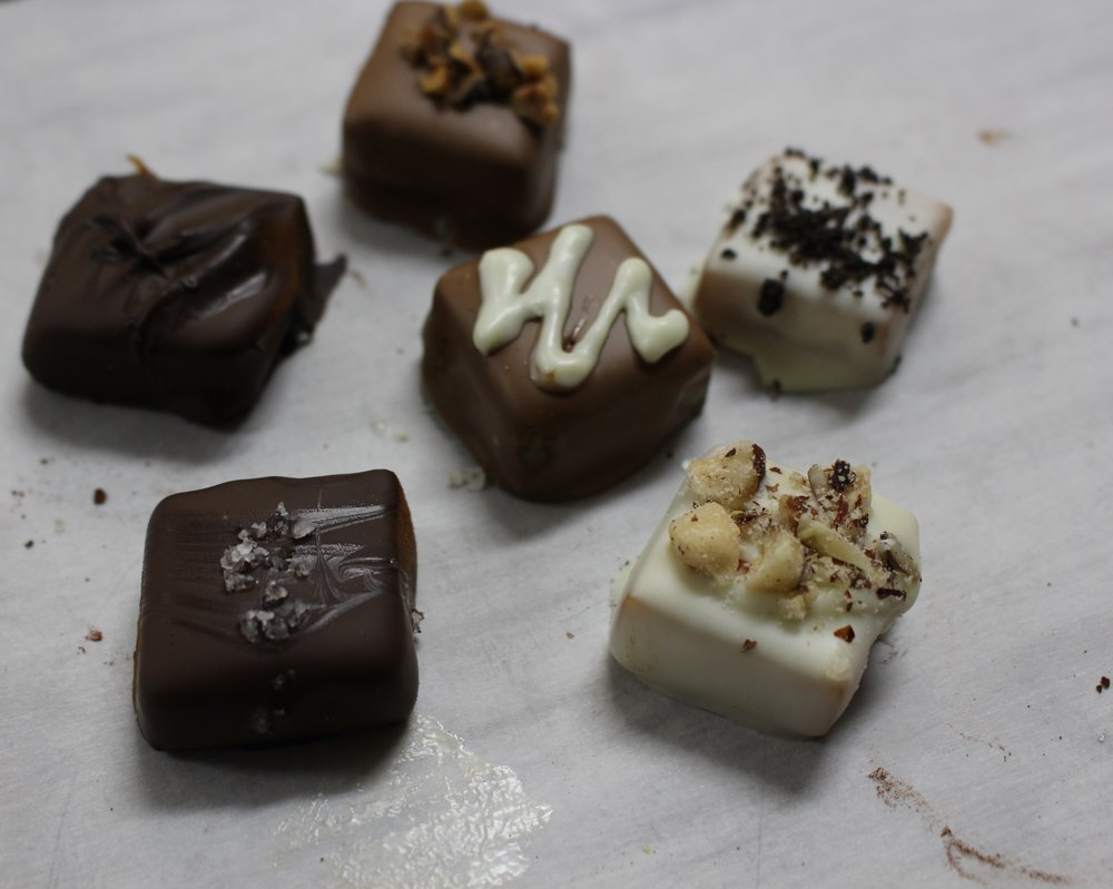 Caramels dipped in chocolate with different toppings