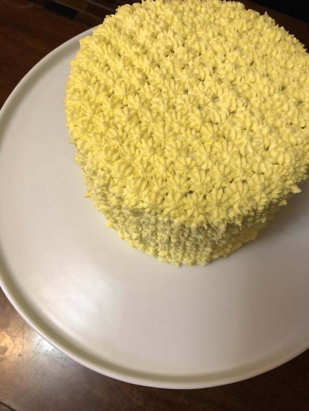 Yellow icing piped in little flowers to give the outside of the cake dimension to look like a pineapple!