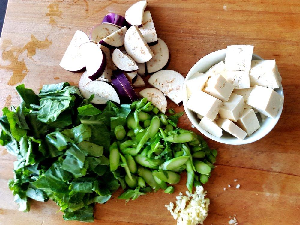 eggplant, tofu, gai lan, and garlic on the cutting board, ready for the wok