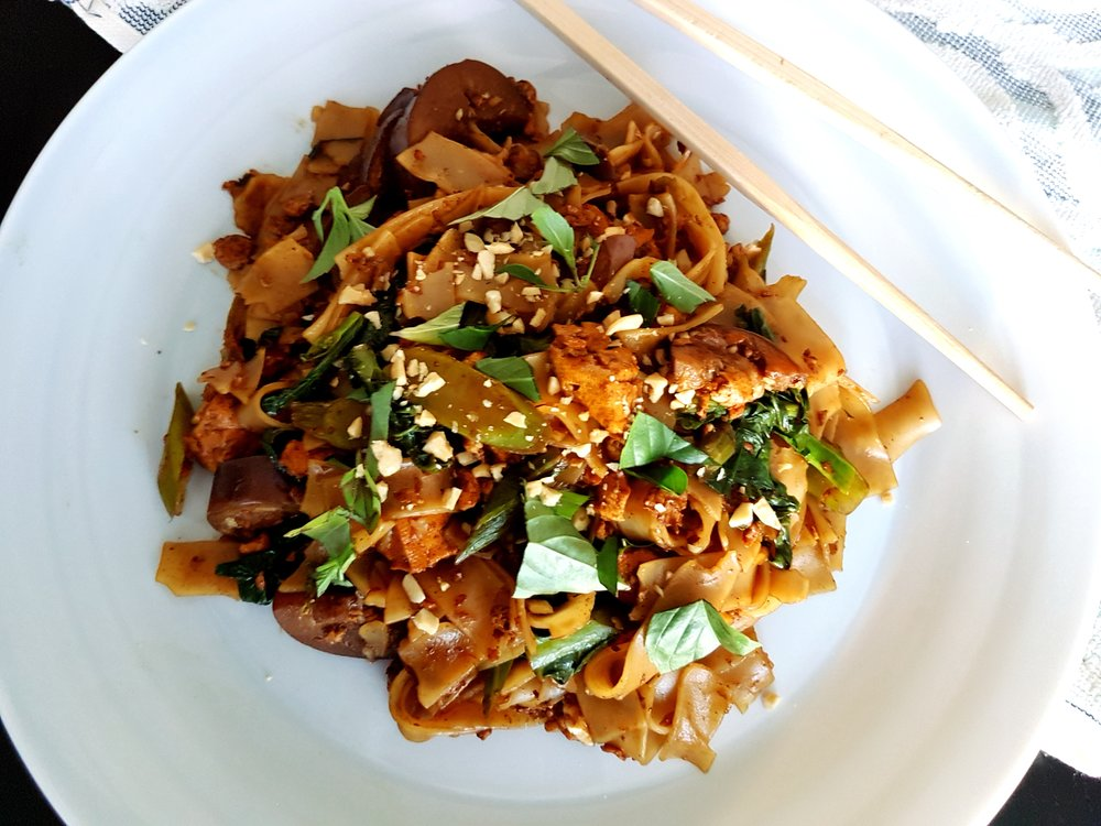 a plate of Vegetarian Pad See Ew hot from the wok, topped with Thai basil, as viewed from above