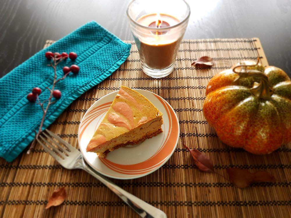 a slice of Baked Pumpkin Cheesecake surrounded by autumn decor