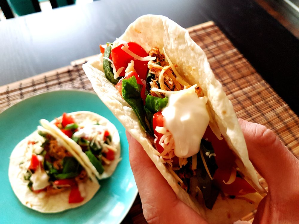 a loaded Fresh Cilantro Lime Chicken Taco being held above the plate showcasing the ingredients within