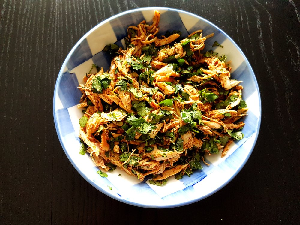 shredded chicken in a bowl mixed with fresh chopped cilantro and a splash of lime