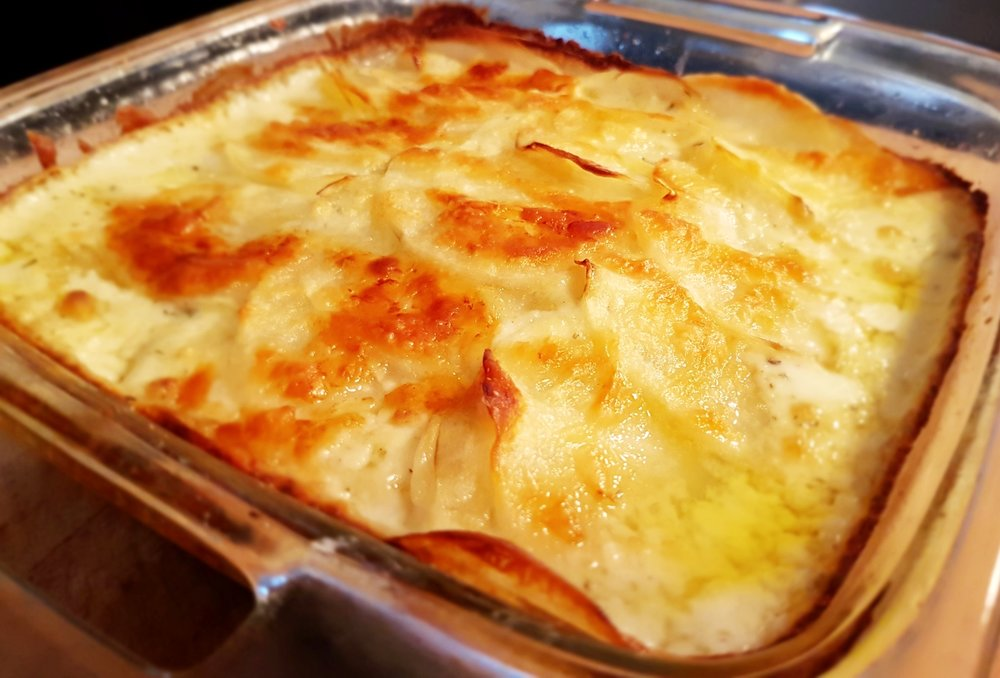 a pan of Creamy Potato Cheese Gratin hot from the oven in a glass baking dish with a layer of bubbling cheese on top