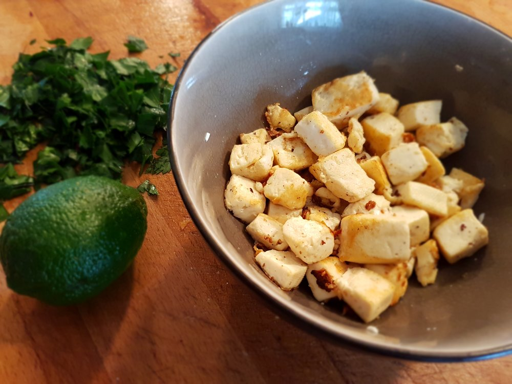 cooked tofu in a bowl with parsley and lime on the side
