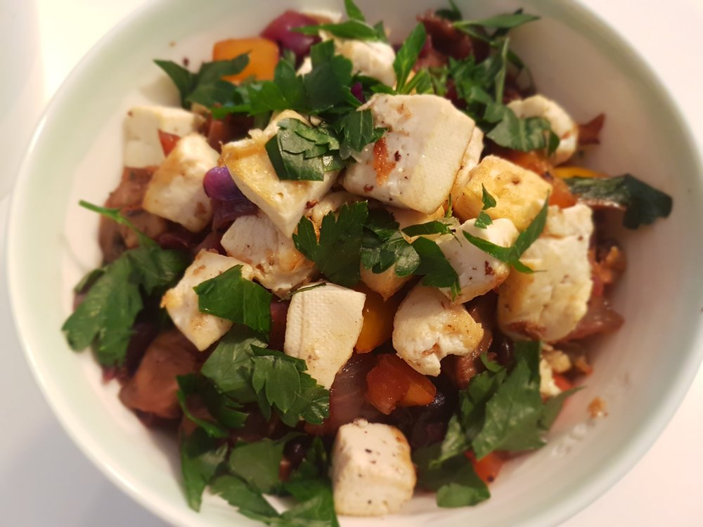 Quinoa with Fresh Vegetables and Tofu ina bowl, topped with parsley