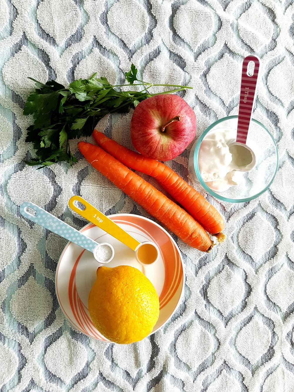 carrots, an apple, a lemon, Greek yogurt, and parsley gathered together for a Healthy Apple Carrot Slaw