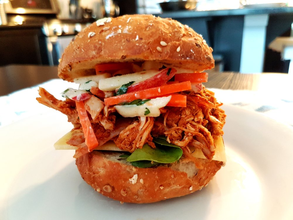 a fully-assembled Spiced Chicken with Apple-Carrot Slaw Sandwich on a multigrain bun