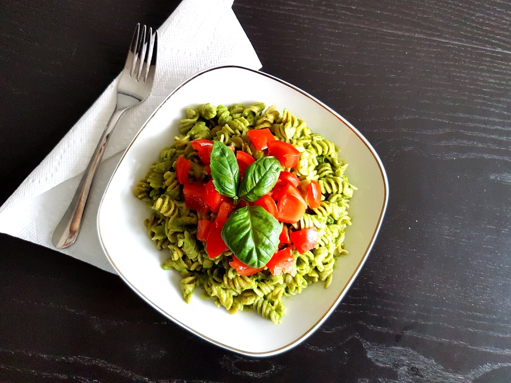 an overhead shot of Vegan Avocado Pesto Pasta topped with fresh tomatoes and basil
