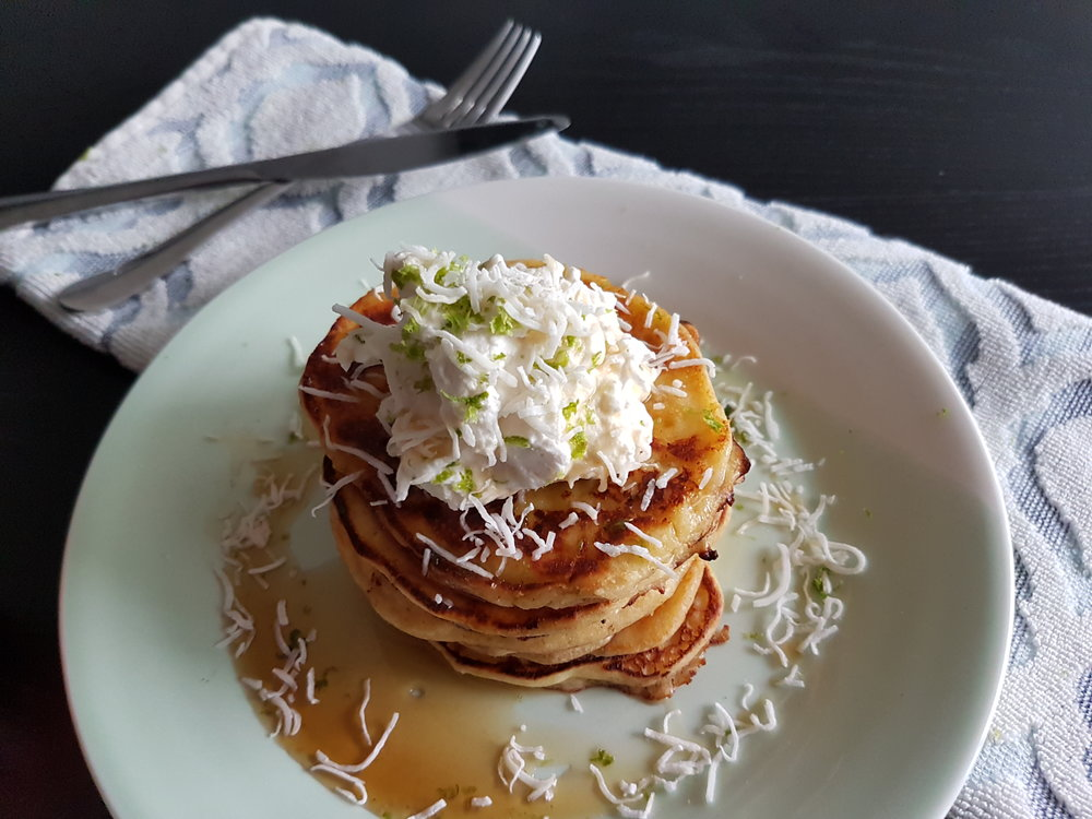 Coconut Lime Ricotta Pancakes topped with whipped cream, maple syrup, and lime zest