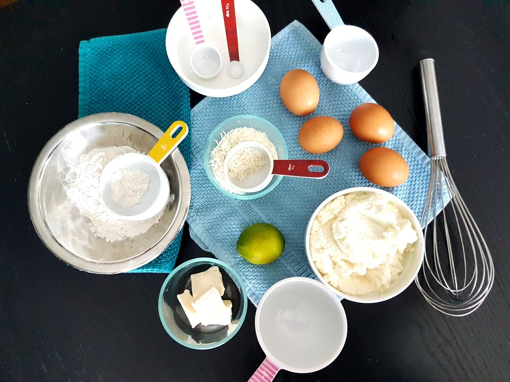 Bowls of ricotta, flour, butter, and coconut accompanied by lime and eggs; all of the ingredients needed to make buttery coconut lime ricotta pancakes.