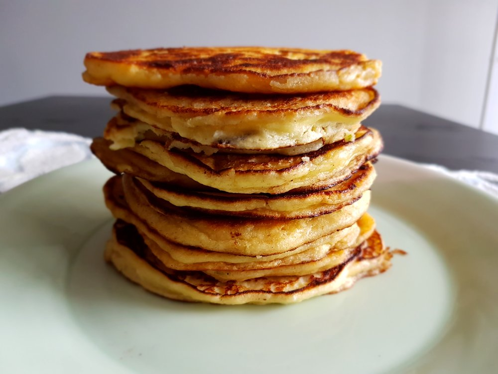 Coconut Lime Ricotta Pancakes piled high on the plate, ready for topping