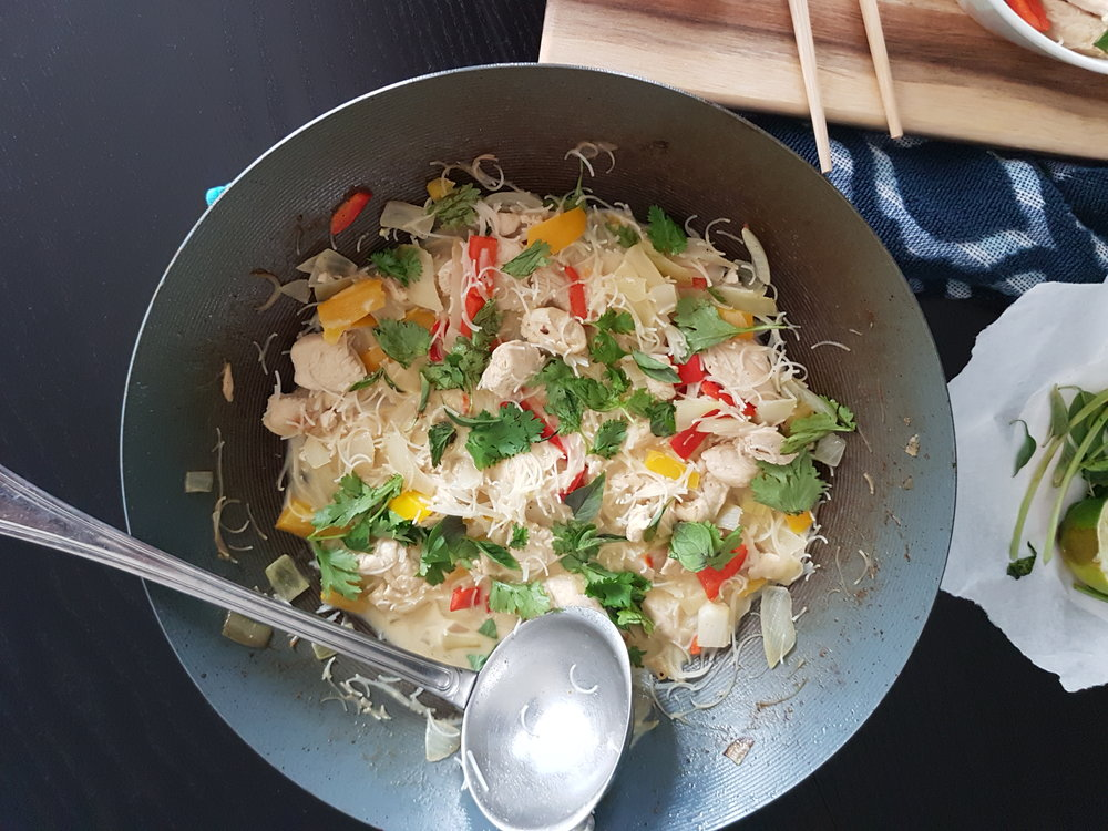 Thai Green Coconut Curry Chicken with Rice Noodles in a wok
