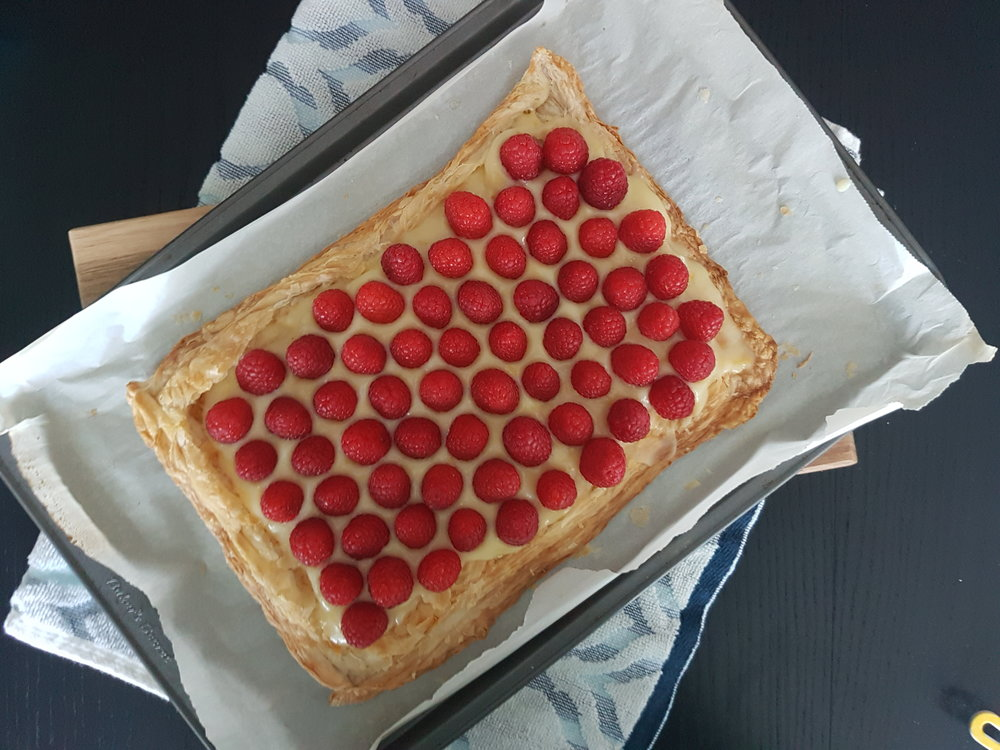 an overhead shot of a Fresh Raspberry Lemon Curd Tart on a baking sheet