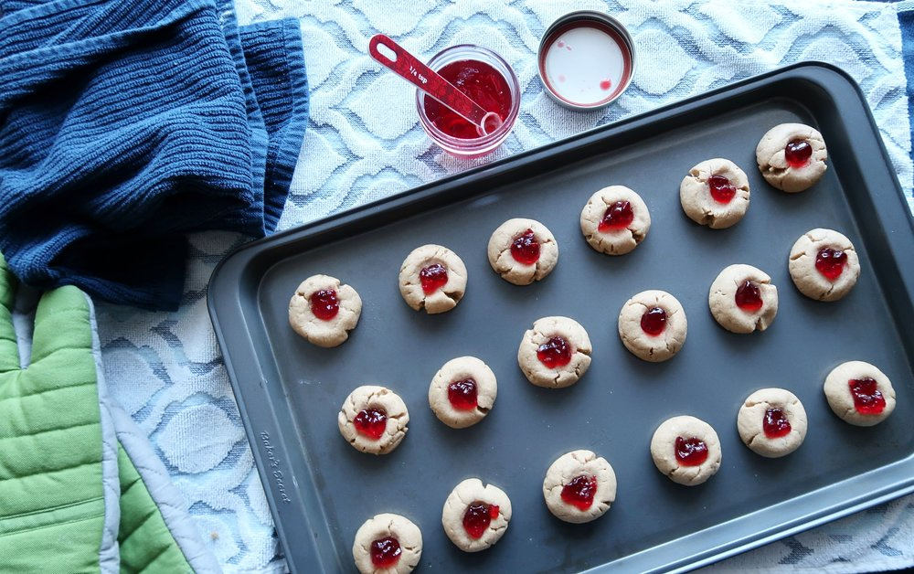 A baking sheet full of Peanut Butter and Jelly Thumbprint Cookies.