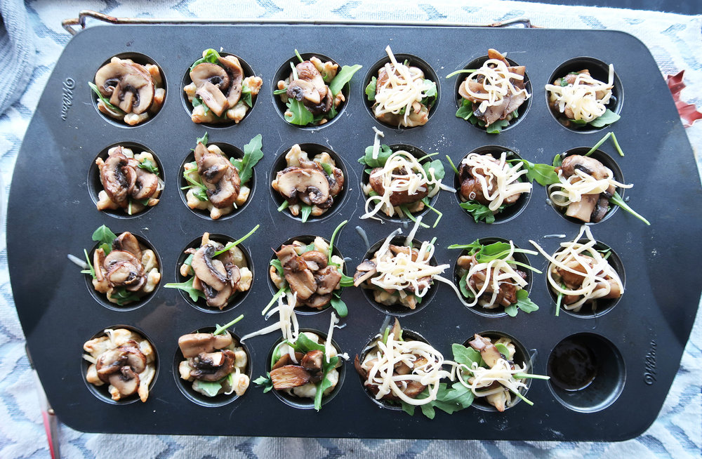 Mushroom arugula tarts topped with green onions and cheese.