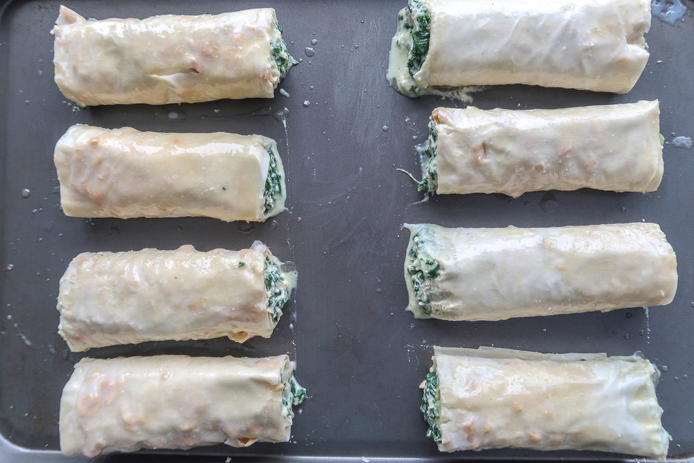 Spanakopita rolls on a baking sheet.