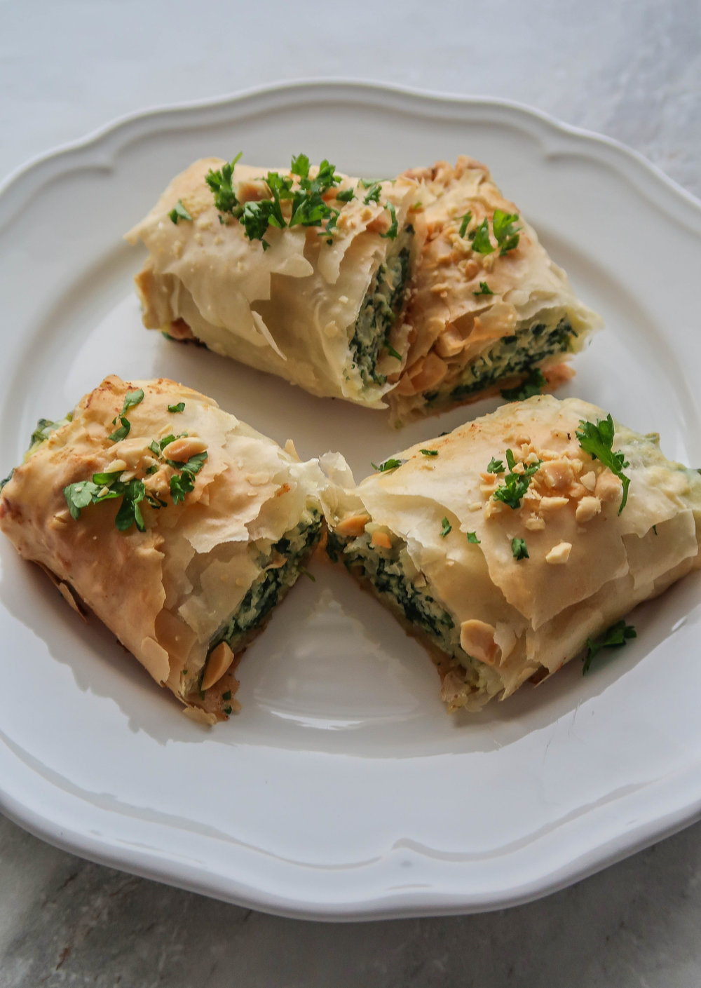 A plate with four Spinach and Ricotta Spanakopita Roll halves.