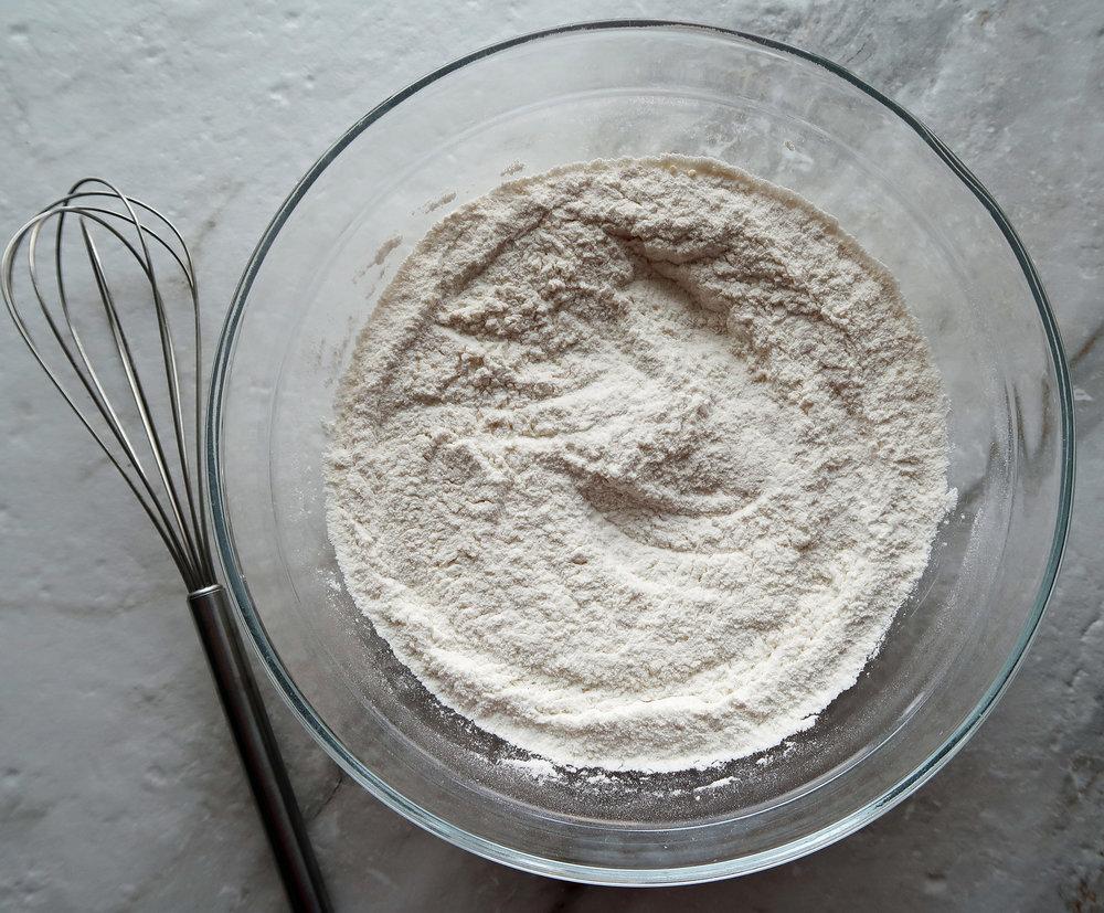 Flour, parmesan, and baking powder in a bowl.