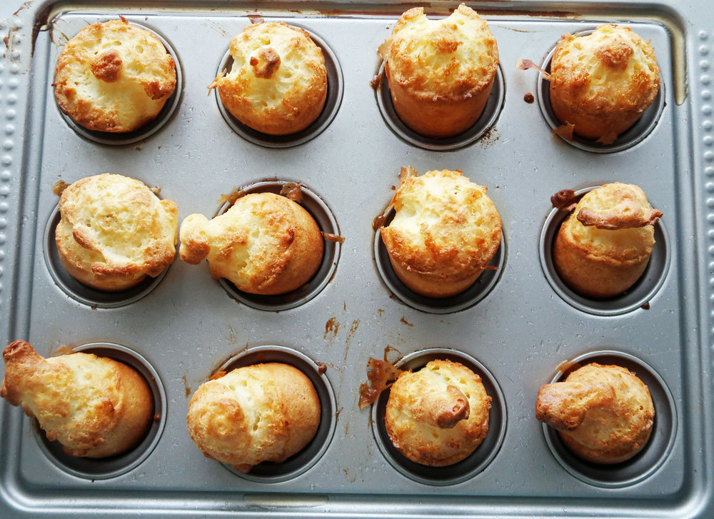 A pan of popovers with golden-brown tops.