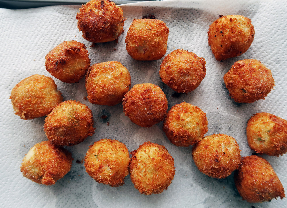Crispy mashed potato cheese balls cooling on a paper towel.