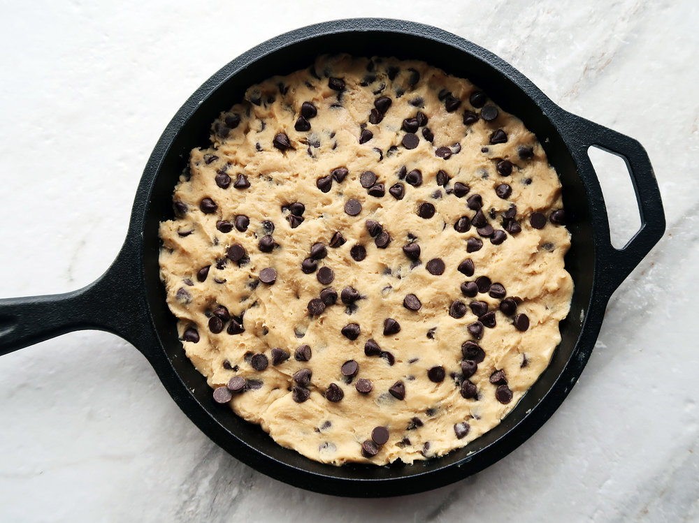 Chocolate chip cookie dough in a cast iron skillet.