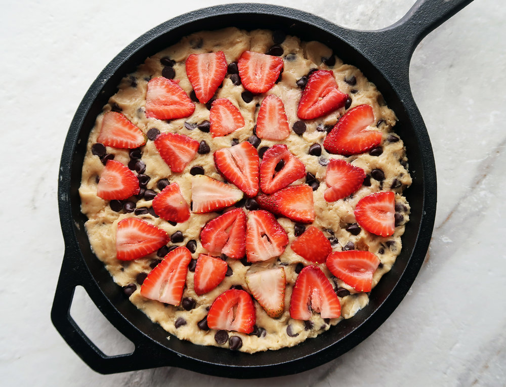 Cookie dough in a skillet topped with strawberries.