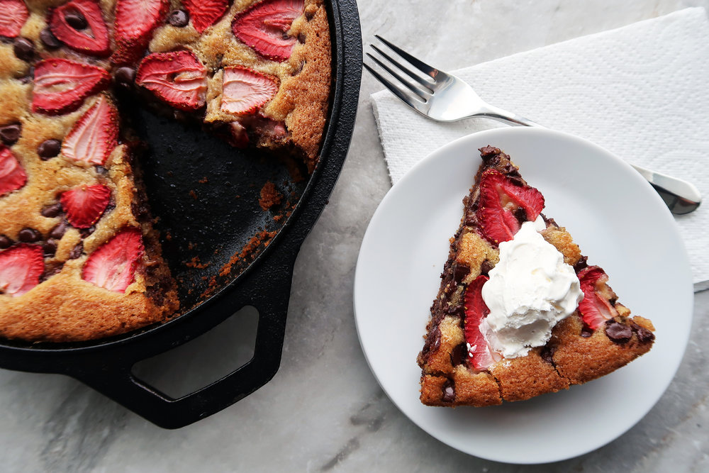 A slice of Strawberry Chocolate Chip Skillet Cookie topped with whipped cream.