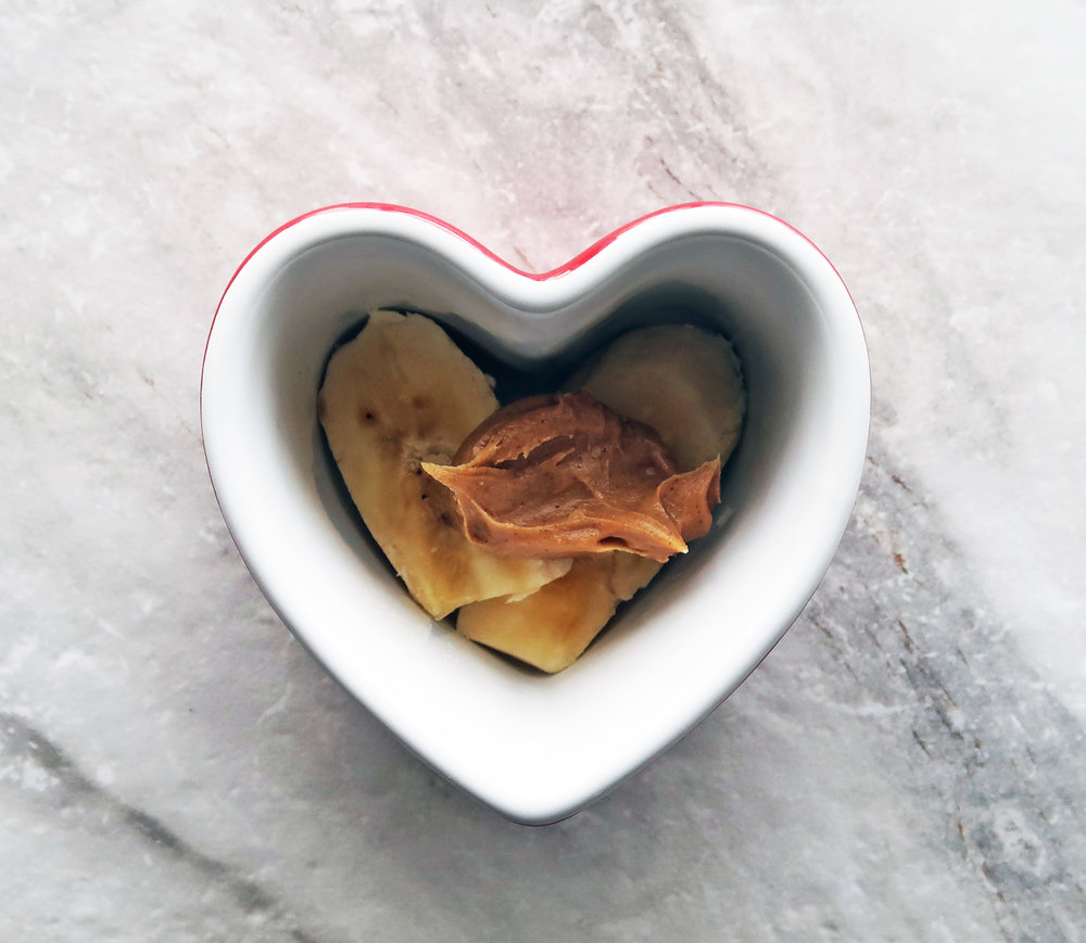 Bananas topped with peanut in a heart-shaped ramekin.