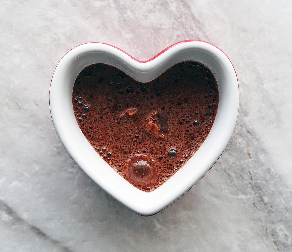 Chocolate cake batter in a heart-shaped ramekin.
