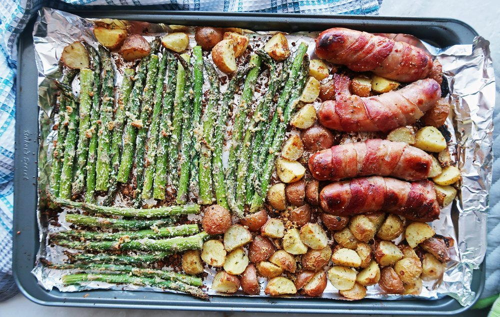 A sheet pan meal featuring roasted sausages, potatoes, and asparagus.