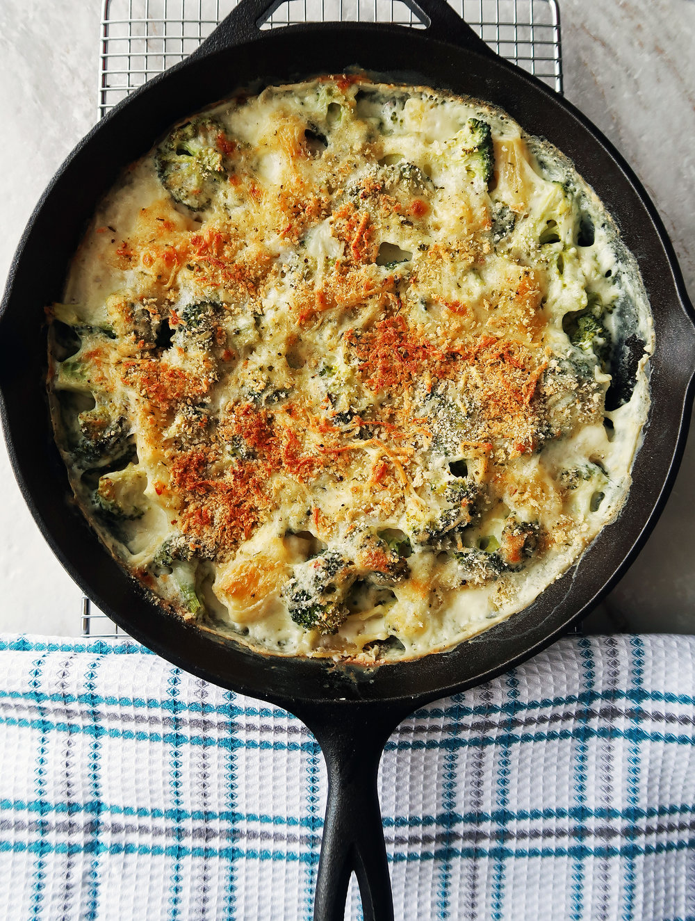 One Skillet Pasta Bake with Broccoli and White Cheese Sauce cooling on a rack.