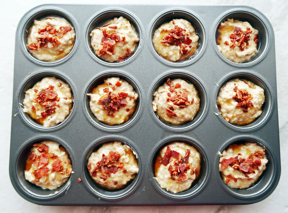 Muffin batter in a baking pan topped with bacon pieces.