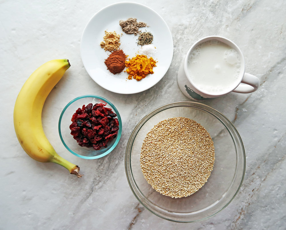 Bowls of uncooked quinoa, dried cranberries, spices, coconut milk, and a banana.