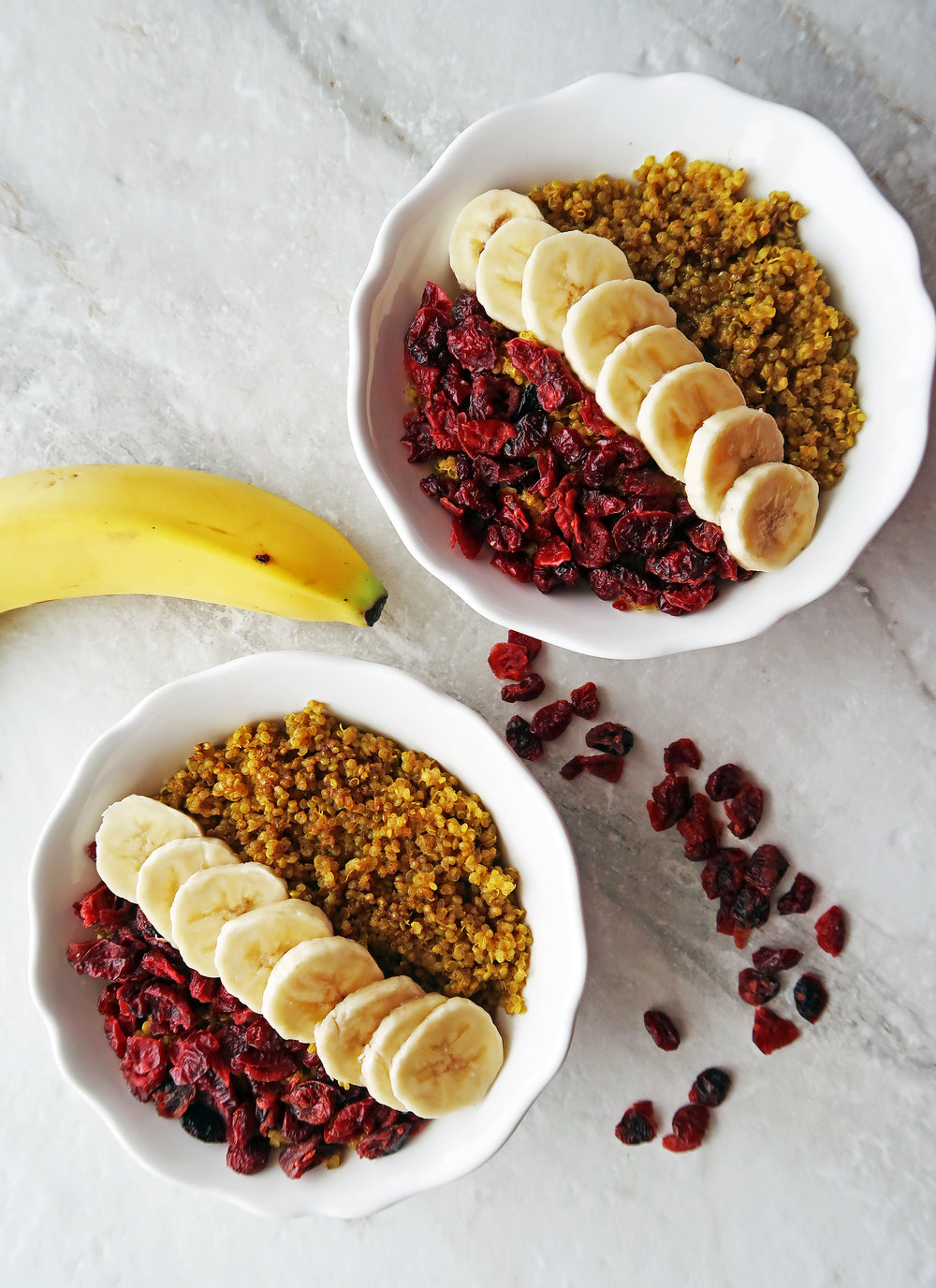 Two Golden Milk (Turmeric Latte) Quinoa Bowls with dried cranberries and banana slices.