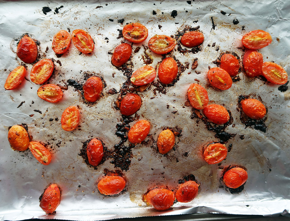 Roasted cherry tomatoes with garlic on a baking sheet.