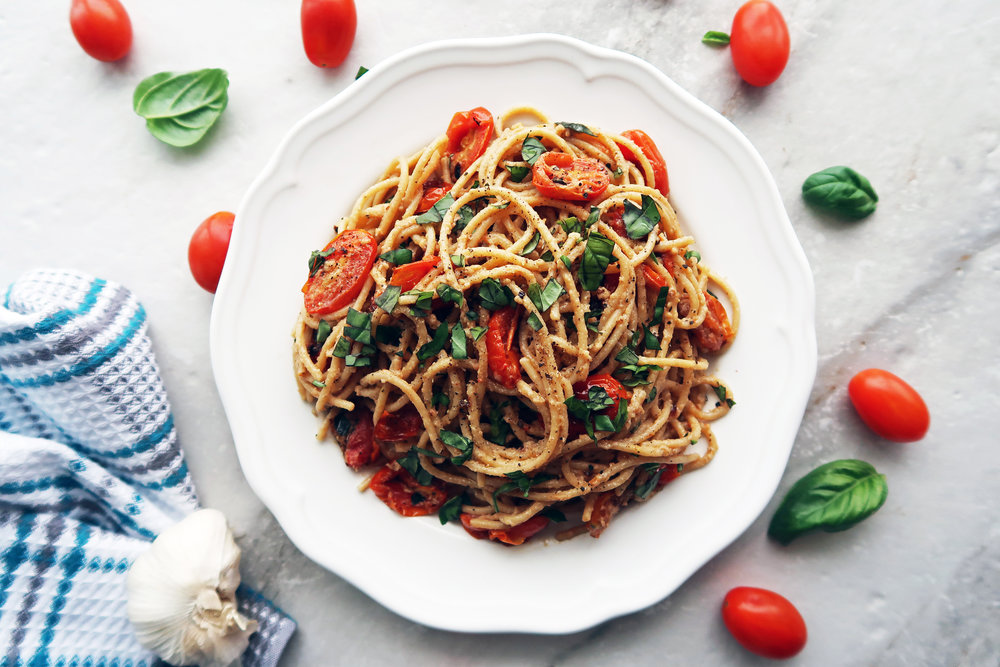 Black Pepper and Parmesan Spaghetti with Garlic Roasted Tomatoes and basil on a white plate.