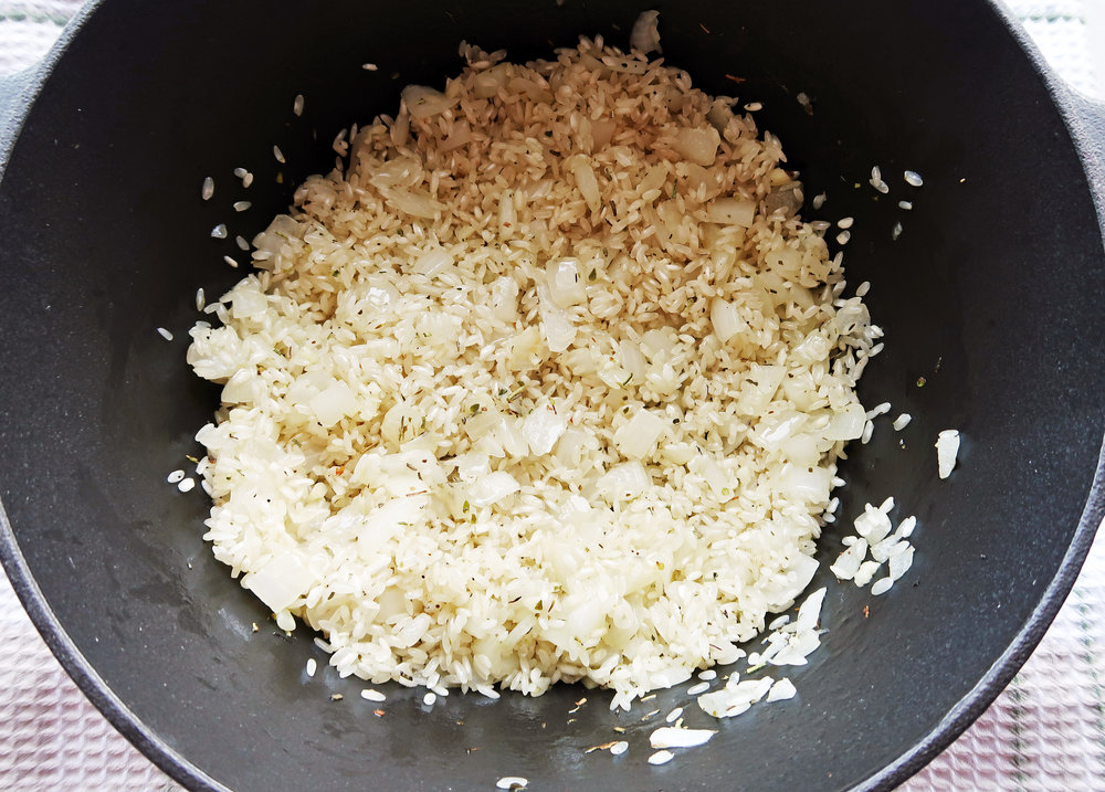 A Dutch oven containing arborio rice, onion, and herbs.