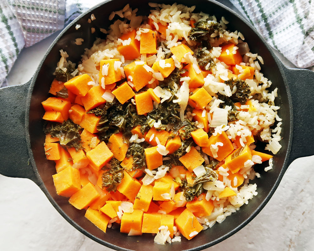 A Dutch oven full of vegetarian, gluten-free sweet potato and kale baked risotto.