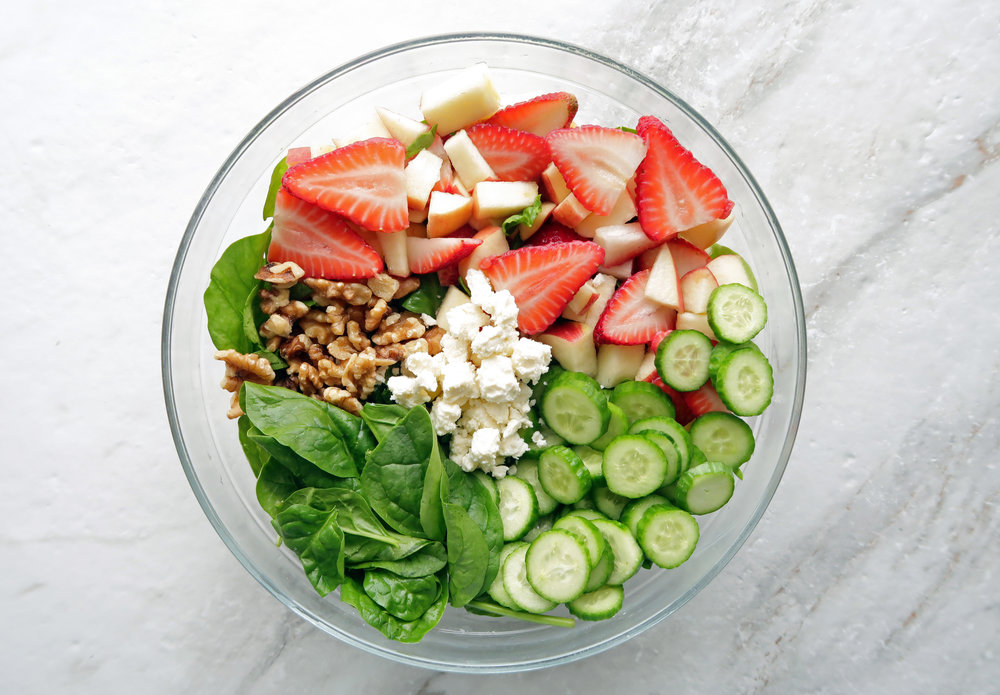 Strawberry Cucumber Spinach Salad with feta and walnuts in a large glass bowl.