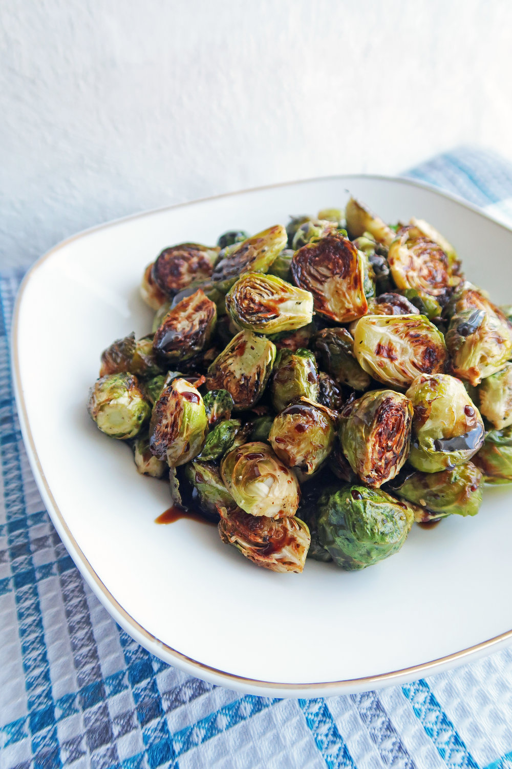 Simple and easy, gluten-free and vegan Roasted Brussels Sprouts with Balsamic-Maple Glaze on a white plate.