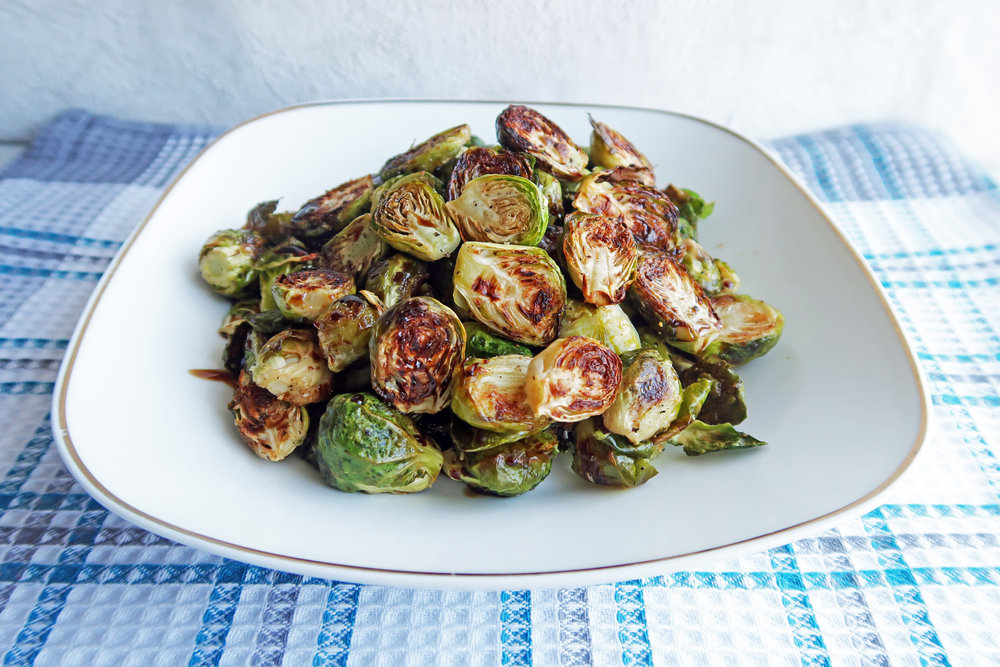 Side view of gluten-free and vegan Roasted Brussels Sprouts with Balsamic-Maple Glaze on a white plate.