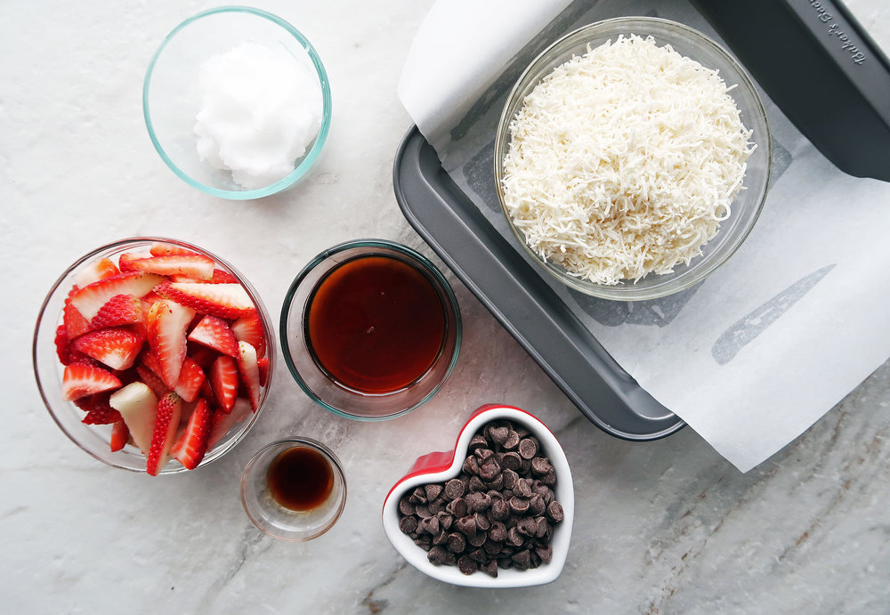 Bowls of strawberries, chocolate chips, maple syrup, and shredded coconut.