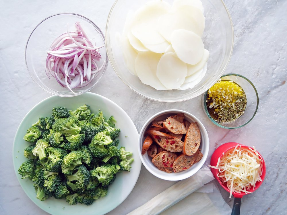 Bowls of broccoli, sliced potatoes, sausage, red onions, and grated cheese.